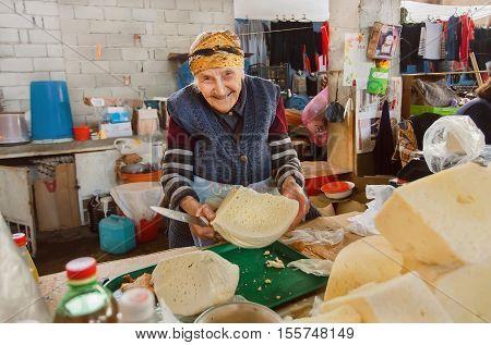 SIGNAGI, GEORGIA - OCT 7, 2016: Older happy woman sells organic homemade cheese on Georgian village farmer's market on October 7, 2016. Signagi of Kakhetia has a population 2.200