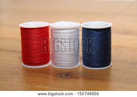 Red White And Blue Cotton Reels Or Bobbins On A Wooden Needlework Table