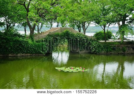 An arched stone bridge over a small pond within the Lake Tai or Taihu scenic area on Turtle island in Wuxi China on a sunny day in Jiangsu province.