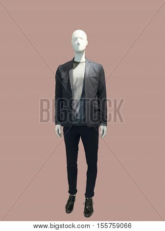 Full-length male mannequin dressed in suit over brown background. No brand names or copyright objects.