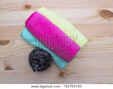 Microfiber cleaning napkins and metallic kitchen sponge on a wooden background.