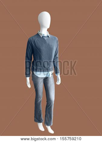 Full-length male mannequin dressed in jumper and jeans over brown background No brand names or copyright objects.