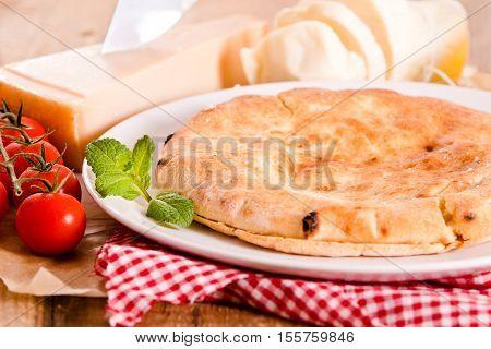 Cheese focaccia bread with cherry tomatoes on white dish.