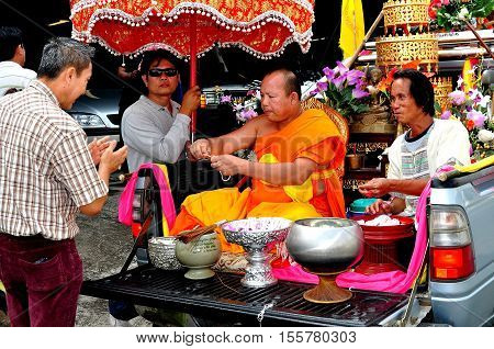 Chiang Mai Thailand - December 25 2012: Buddhist monk seated in the back of a pickup truck offers blessings to the faithful who stop to give alms when the truck makes a stop on a local roadway