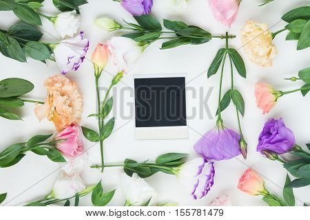 Pink, white and violet eustoma flowers frame with one instant photo