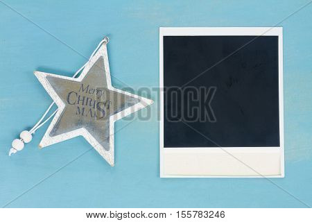 Blue and white christmas with star and instant photo on blue wooden background