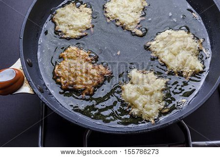 Frying latkes with raw side up and one turned in deep oil on pan on stove from above