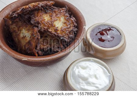 Latkes in a ceramic rustic brown bowl with sour cream and strawberry jam aside from side