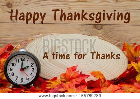 Happy Thanksgiving message Some fall leaves an alarm clock and wood plaque on weathered wood with text A time of Thanks