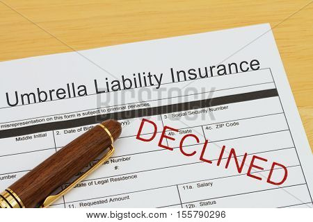 Applying for a Umbrella Liability Insurance Declined Umbrella Liability Insurance application form with a pen on a desk with an declined stamp