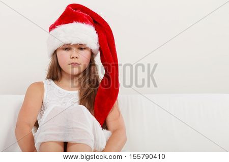 Lonely depressed cute little girl kid in red santa claus hat and white dress. Chrtistmas holiday season.
