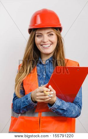 Woman construction worker builder structural engineerin in orange vest red hard helmet holds pen file pad. Safety in industrial work. Studio shot on gray