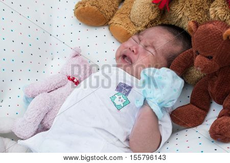 Cute little newborn unsleep and crying on the bed