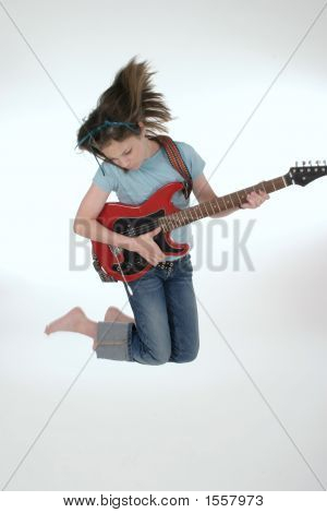 Young Pre Teen Playing Guitar And Jumping
