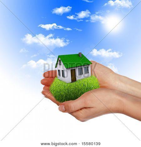 A casa nas mãos contra o céu azul como um símbolo do negócio imobiliário.