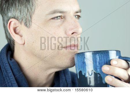 Ruhiger Mann, der Becher suchen Sie Kamera hält