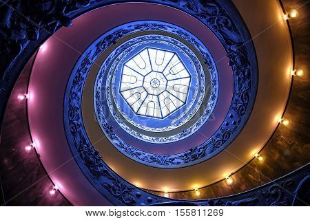 VATICAN CITY - MARCH 24, 2015: the famous stairs,  the Vatican spiral staircase with warm lights on March 24, 2015. The Spiral staircase was designed by Giuseppe Momo in 1932 and located in the Vatican Museums in Vatican City, Rome, Italy