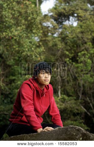 Asian man kneeling on rock outdoors