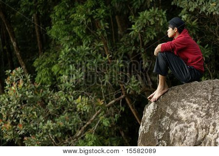Lonely asian man sitting on rock outdoors