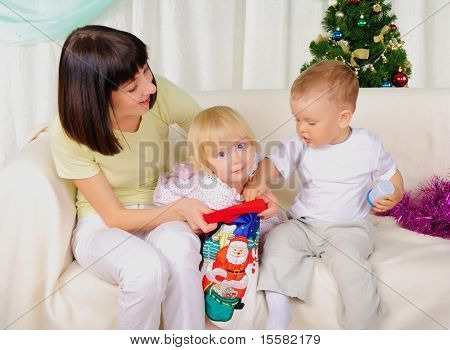 Young mother and her two children - a son and daughter together preparing for the holiday together. Happy New Year!