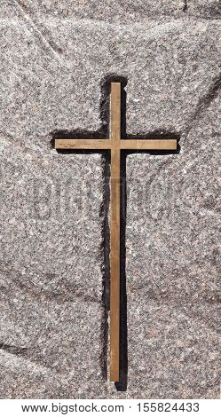 photographed close-up wooden Christian Catholic cross fixed in stone