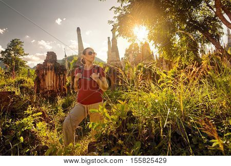 Woman traveling with backpack and looks at sunset among ancient Buddhist stupas of the temple complex In Dein Inle Lake. Birma