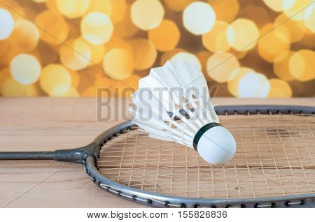 The Badminton White Shuttlecock And Racket On Wooden With Yellow Bokeh Lighting Background
