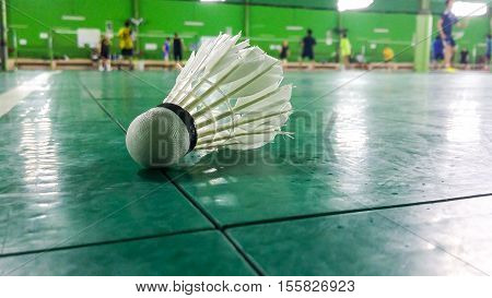 The White Shuttlecock On Badminton Courts With Players Competing