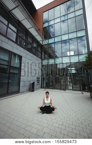 Businesswoman performing yoga in office premises