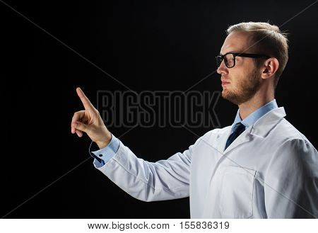 healthcare, people, profession and medicine concept - close up of male doctor touching something imaginary over black background