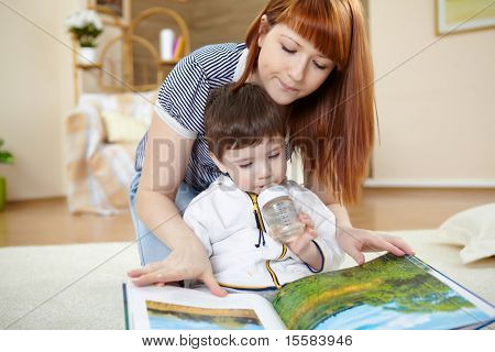 mother playing with her little son at home on the floor
