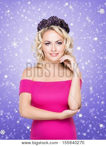 Beauty portrait of attractive blond girl with curly hair and a beautiful headband over purple winter background. Christmas concept.