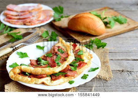 Homemade bacon omelette. Delicious omelette stuffed with bacon and parsley on a plate, bacon slices on a plate, bread roll, fork, knife, cutting board, fresh parsley sprigs on old wooden background
