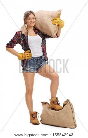 Full length portrait of a female agricultural worker with a burlap sack on her shoulder and under her foot isolated on white background