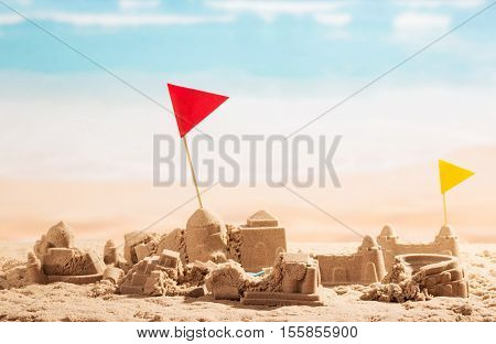 Dilapidated sand castles, towers and flags Coliseum on the background of the sea.