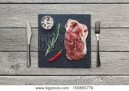 Raw beef steak in craft paper on dark wooden table background, top view. Fresh juicy meat with rosemary and chili peppers and cutlery on stone board. Cooking ingredients, butcher's and grocery concept