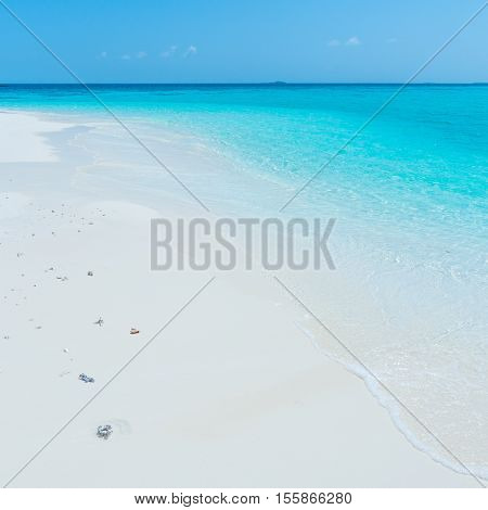 Tropical island in the Indian Ocean. White sand beach blue sky and a strip of ocean