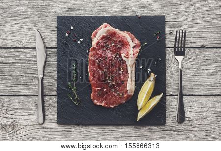 Raw beef steak in craft paper on dark wooden table background, top view. Fresh juicy meat with rosemary and pepper, lemon and cutlery on stone board. Cooking ingredients, butcher's and grocery concept