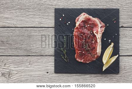 Raw beef steak in craft paper on dark wooden table background, top view. Fresh juicy meat with rosemary and lemon on stone board. Cooking ingredients, butcher's and grocery concept, copy space