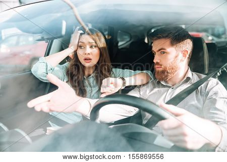 Couple have a dispute in car. woman holding her head