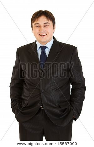 Pleased businessman keeping his hands in trousers pockets isolated on white