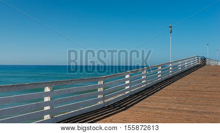 Wooden pier and ocean to the horizon. Decreases  diminishing perspective.