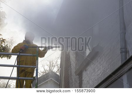 man in yellow rain suit cleans paint from brick wall of house facade with pressure washer while standing on scaffolding