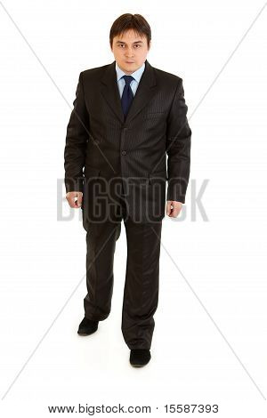 Full length portrait of concentrated businessman making first step isolated on white