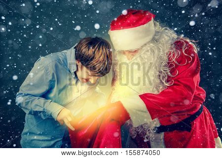 Authentic Santa Claus and a teenager. Santa Claus brought gifts.