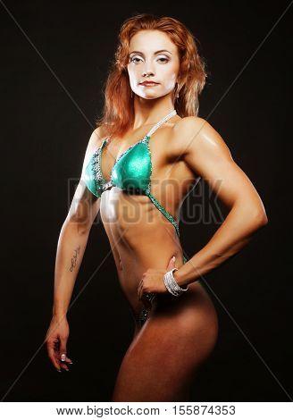 Sexy blond bodybuilder woman in bikin on black background