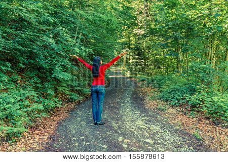 Woman in the forest on the edge. She raised her hands up in an appeal to nature. Sun rays in the trees. Further prospects of the road.