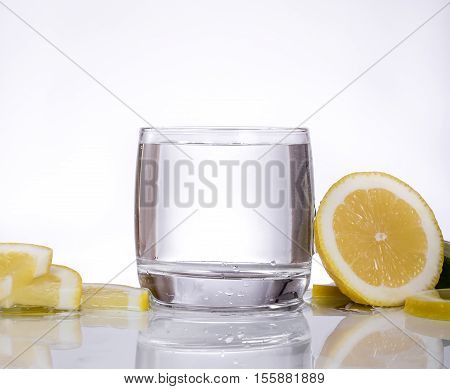 Splashes of water lemon falling into a glass isolated reflection white background water drops