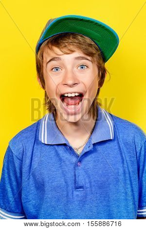 Portrait of a shouting teenage boy over yellow background. Studio shot. Teenager awkward age.