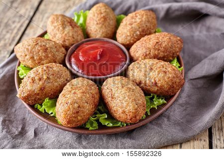 Kibbeh traditional middle eastern homemade beef, lamb, goat or camel meat stuffed bulgur kofta spicy meatball croquettes on green salad food on vintage wooden table background